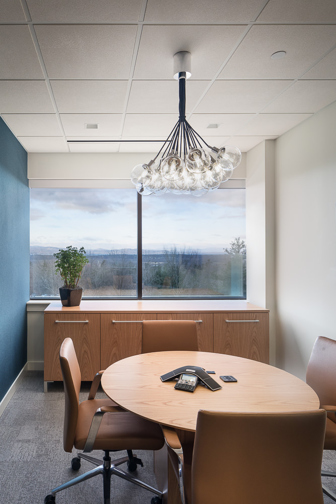 A small conference room includes a navy accent wall and a globe cluster pendant light for a modern look.